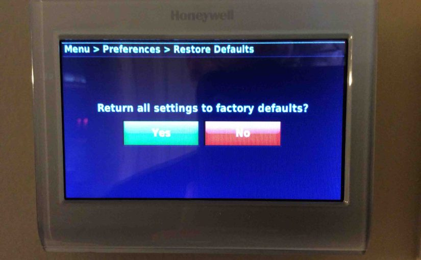 Picture of the Honeywell RTH9580WF Smart Thermostat, displaying the Restore Factory Defaults confirmation screen.