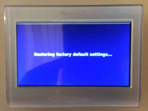 Reset Honeywell thermostat settings: Picture of the Honeywell RTH9580WF smarttThermostat, showing the Restoring Factory Default Settings screen during reset.