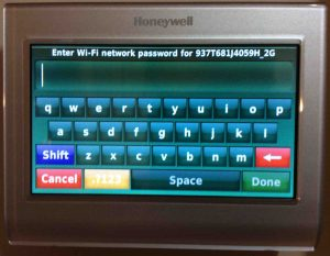Picture of the t-stat , showing the WiFi Network Password Entry screen.