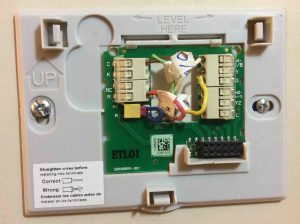 Picture of the Honeywell Smart Thermostat RTH9580WF wall plate, mounted, with wires connected.