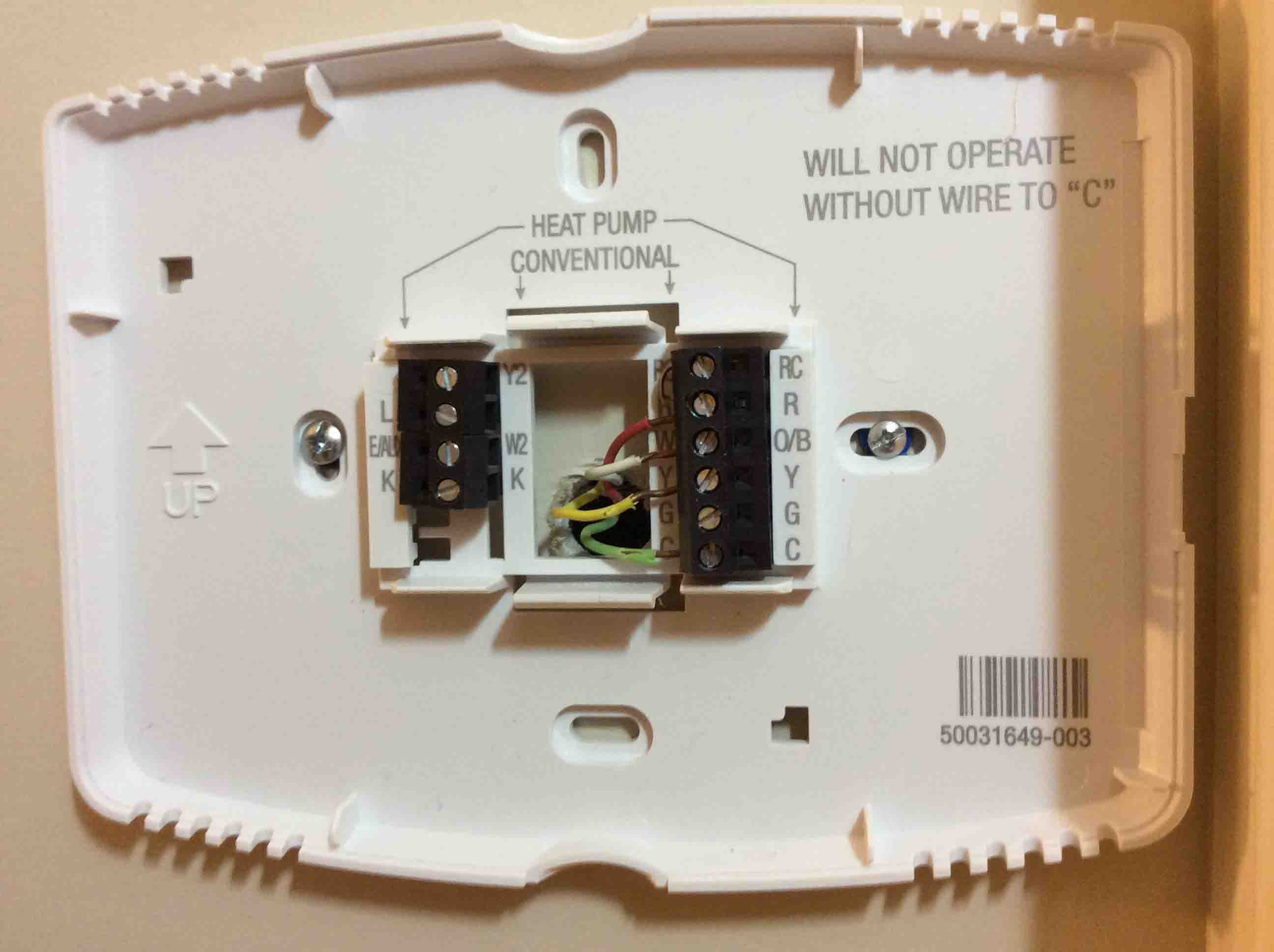 Picture of a Honeywell WiFi thermostat wall plate, showing a typical wiring  hookup.