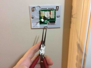 Picture of needle nose pliers being used to straighten the ends of thermostat wires before connecting them to the new wall plate terminals.