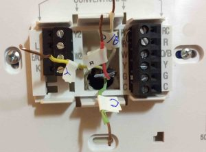 Picture of a Thermostat Wall Plate with wires labeled and disconnected.