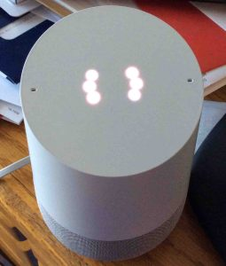 How to factory reset Google Home. Picture of the original Google Home speaker, factory default reset in progress, displaying white spinning light ring pattern.
