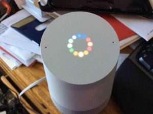 Picture of the Google Home speaker, booting in progress, displaying the multi colored light ring, indicating that.