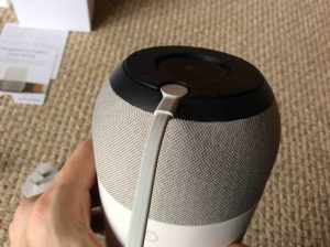Picture of the Google Home speaker, bottom view, showing the power plug fully inserted into speaker power port.