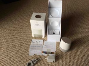Picture of the Google Home intelligent speaker, completely unboxed, showing the original packaging opened, the speaker, manuals, and power adapter.