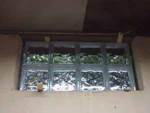 Picture of the Basement glass block window replacement 1, positioned in exterior wall hole and shimmed, prior to mortar application.