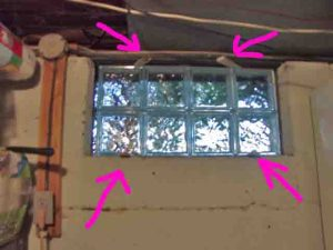 How to install glass block windows. Picture of the basement glass block window replacement 2, positioned and shimmed, with shims highlighted.