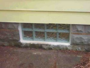 Picture of the basement glass block window replacement 8, shims removed, installation complete, exterior view.