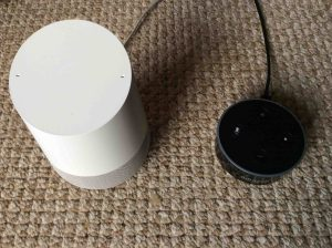 Picture of a Google Home speaker and an Amazon Dot speaker, side-by-side. Google Home Vs. Amazon Alexa. Amazon Alexa Echo Dot speaker picture gallery.