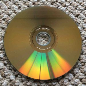 How to fix a scratched DVD movie disc. Picture of the Slightly dusty dual layer DVD disc, showing the gold data side