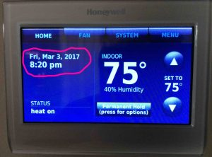 Picture of the Honeywell RTH9580WF Wi-Fi thermostat, displaying its -Home- screen, as it appears with no internet connection, with the manually set time and date highlighted.