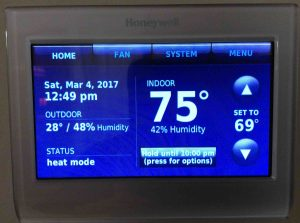 Picture of the Honeywell RTH9580WF wireless thermostat, displaying its -Home- screen, with the temperature set to 69 degrees, and in temporary hold until 10:00 PM.