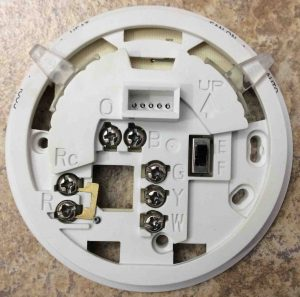 Picture of the Honeywell T8775C1005(2) thermostat wall plate, front view, showing screw terminal connection points.