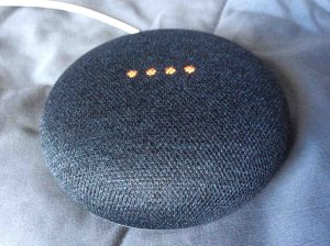 Picture of the Google Home Mini smart speaker, top front view.