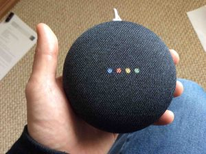 Picture of the Google Home Mini speaker, displaying multi colored lights during reboot.