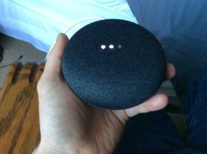 Picture of the Google Home Mini smart speaker, factory default reset in progress, showing scanning bright white lights.