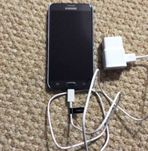 Front view picture of the smart phone, front view, with the wall charger connected. Unboxing Samsung Galaxy J7.