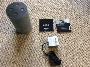 Picture of the Amazon second generation Echo speaker with all accompanying accessories unboxed.