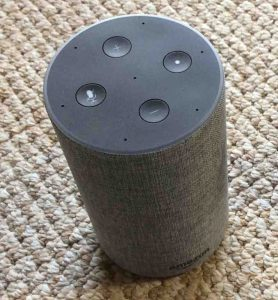 Picture of the Amazon Echo 2nd generation smart speaker, top view, showing the light ring and the volume, mic mute, and action buttons for Alexa features control.