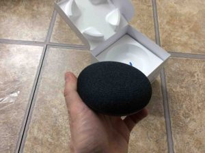 Picture of the Google Home Mini smart speaker, removed from original box, held in hand.