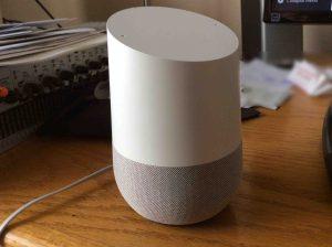 Picture of the original Google Home smart speaker, front left view, sitting on desk.