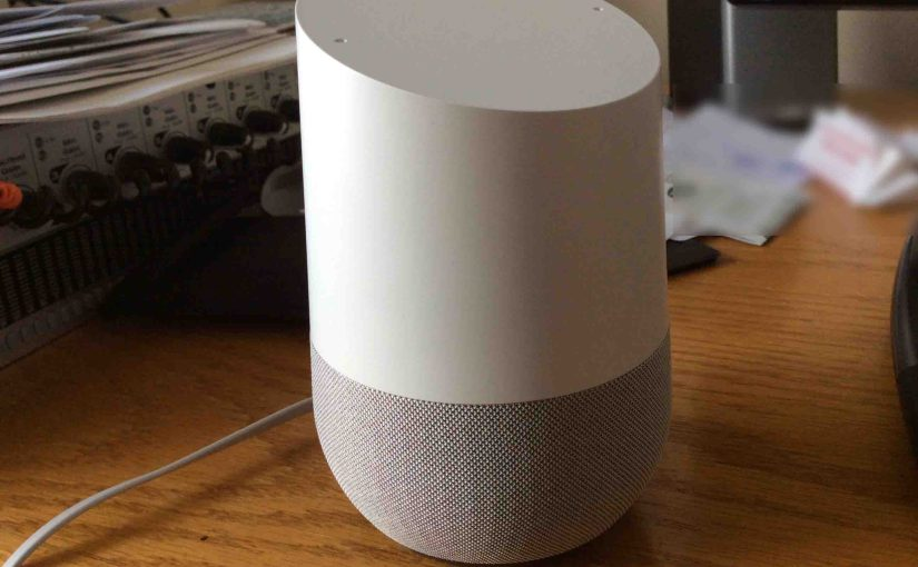 Picture of the original Google Home smart speaker, front left view, sitting on desk.