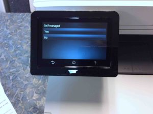 Picture of the HP Color Laserjet M477 printer, displaying its - Default Settings->Self Managed- confirmation screen.