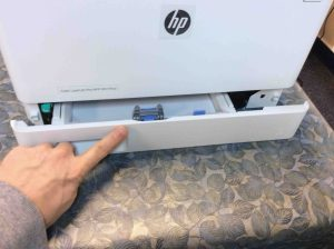 Picture of the HP Color Laserjet Pro MFP M477 FNW printer, front view, closing lower paper tray.