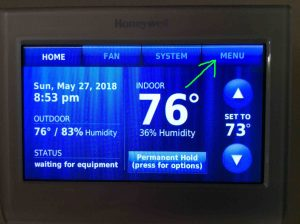 How to find Honeywell RTH9580WF thermostat IP address, MAC ID, and MAC CRC values.  Picture of the Honeywell RTH9580WF WiFi thermostat, showing its -Home- screen, with the -Menu-button highlighted.