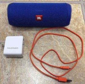 Picture of the JBL Flip 4 portable speaker with a RavPower USB charger and micro USB charge cable.