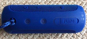 Picture of the JBL Flip 4 Bluetooth speaker, top view, showing speaker controls, horizontal.