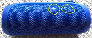 Picture of the JBL Flip 4 Bluetooth speaker. Showing the Volume UP and Play-Pause buttons circled in yellow. JBL Flip 4 buttons layout.