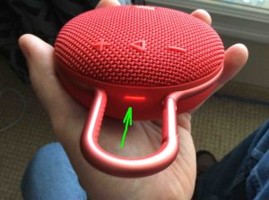 Picture of the JBL Clip 3 Bluetooth wireless speaker, top view, status lamp glowing red.