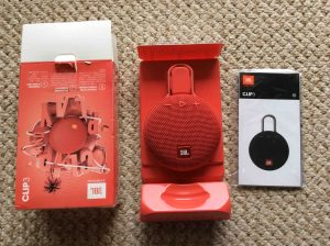 Picture of the JBL Clip 3 portable speaker package, unpacked, showing its contents. JBL Clip 3 waterproof Bluetooth speaker review specs features.