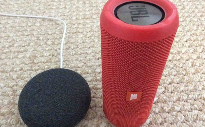 Picture of a Google Home Mini smart speaker alongside a JBL Flip 3 Bluetooth speaker.