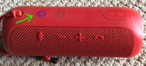 Picture of the JBL Flip 3 battery powered Bluetooth speaker, showing its power button glowing blue.
