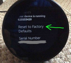 Picture of the Amazon Echo Spot smart speaker, showing the Reset To Factory Defaults option highlighted on its Device Options screen.