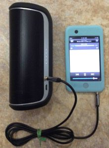 Picture of the JBL Flip 2 Bluetooth speaker, playing from an iPod Touch via its AUX input port. JBL Flip 2 buttons.
