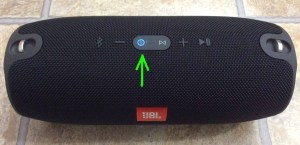 Picture of the JBL Xtreme Bluetooth speaker powered on and paired, with its blue glowing Power button highlighted.
