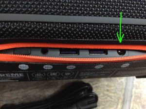 Picture of the JBL Xtreme Bluetooth speaker, rear view, showing its ports zipper open, with the power input charging port highlighted.