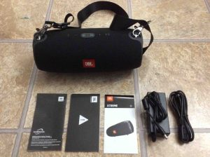 Picture of the Unboxed JBL Xtreme Bluetooth Speaker with charger, strap, and manuals.