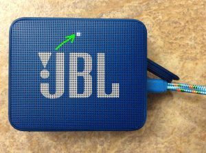 Picture of the Go 2 JBL speaker, front view, powered ON with the charger connected. The Go 2 is showing fully charged, with its steady or blinking white lamp highlighted. It's fully charged in either case.