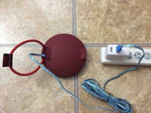 Picture of the UE Roll speaker, back view, connected to USB power and charging.