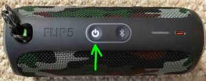 Top view of the speaker, powered ON, not paired, showing the glowing Power button highlighted.