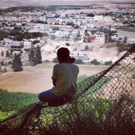 Palestinian Boy in Jericho Sitting on a Fence