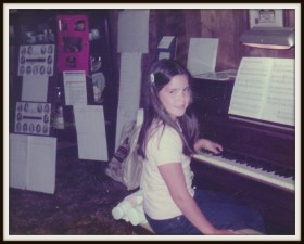 A photograph of Lori at a piano lesson, ca. 1983. She is sitting at the piano, with one hand on the keyboard, and turned to look at the camera.