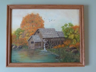 A photograph of an oil painting by Violet Reisig, Lori's maternal grandmother. The painting is of a mill near a body of water, with trees of orange and green.