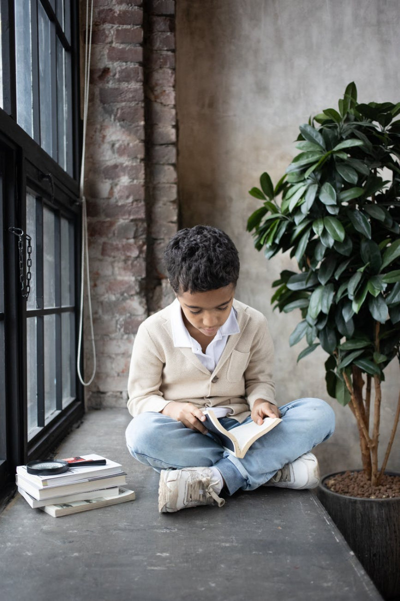 concentrated arabian child reading interesting book while sitting near window